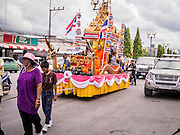 31 OCTOBER 2012 - YALA, YALA, THAILAND:  Thai Buddhists pull a Buddhist monk on a parade float through Yala for Ok Phansa. Ok Phansa marks the end of the Buddhist 'Lent' and falls on the full moon of the eleventh lunar month (October). It's a day of joyful celebration and merit-making. For the members of Wat Kohwai, in Yarang District of Pattani, it was a even more special because it was the first time in eight years they've been able to celebrate Ok Phansa. The Buddhist community is surrounded by Muslim villages and it's been too dangerous to hold the boisterous celebration because of the Muslim insurgency that is very active in this area. This the year the Thai army sent a special group of soldiers to secure the village and accompany the villagers on their procession to Yala, a city  about 20 miles away.  PHOTO BY JACK KURTZ