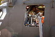 Yong boy examining minigun on MH-53 Chinook at Airventure 2017.