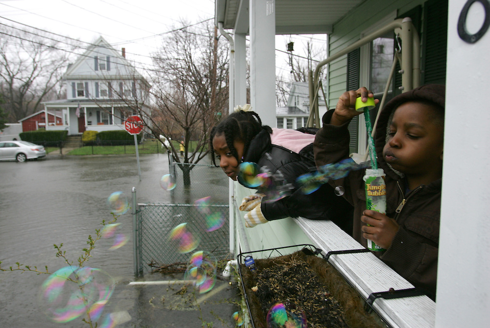 Quincy, MA 03/30/2010.Wendell Jean, age 5, blows bubbles to pass the time while stuck at home with his sister Angie and their mother Mary on Tuesday afternoon.  The Jean family's home on Miller St. in West Quincy was flooded for the second time this month as heavy rains soaked the South Shore again..Alex Jones / The Patriot Ledger