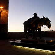 """PITIGLIANO, ITALY - OCTOBER 23: The bronzed sculpture of Villano and his Donkey depicts appreciation for hard working farmers in the Piazza della Repubblica in Pitigliano. Pitigliano is a small village located in Tuscany halfway from Florence and Rome, perched atop a volcanic tufa ridge. Its unmistakable skyline makes it stand out. Pitigliano is a truly unique village in southern Tuscany, in the less-known Maremma district. The town is dubbed """"la citta' di tufo"""" for the rock that it not only is built on.<br /> The village is also called """"Little Jerusalem"""", not just because it looks ancient and bears a resemblance to that city, but also for the long presence of a Jewish community in the town. Pitigliano, Tuscany, Italy. 23rd October 2017. Photo by Tim Clayton/Corbis via Getty Images)"""