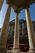 Bank of England  seen through rising pillars and columns of Cornhill Exchange, City of London. We look upwards to the famous Bank of England in the City Of London, the financial district, otherwise known as the Square Mile. A new design Routemaster bus passes under the pillars going eastwards towards Bank Triangle, a busy intersection. With such a wide-angle perspective the bank and its architecture looks powerful and influencial in the UK's economy. The tall pillars rise above and makes for a scene of stability and strength.