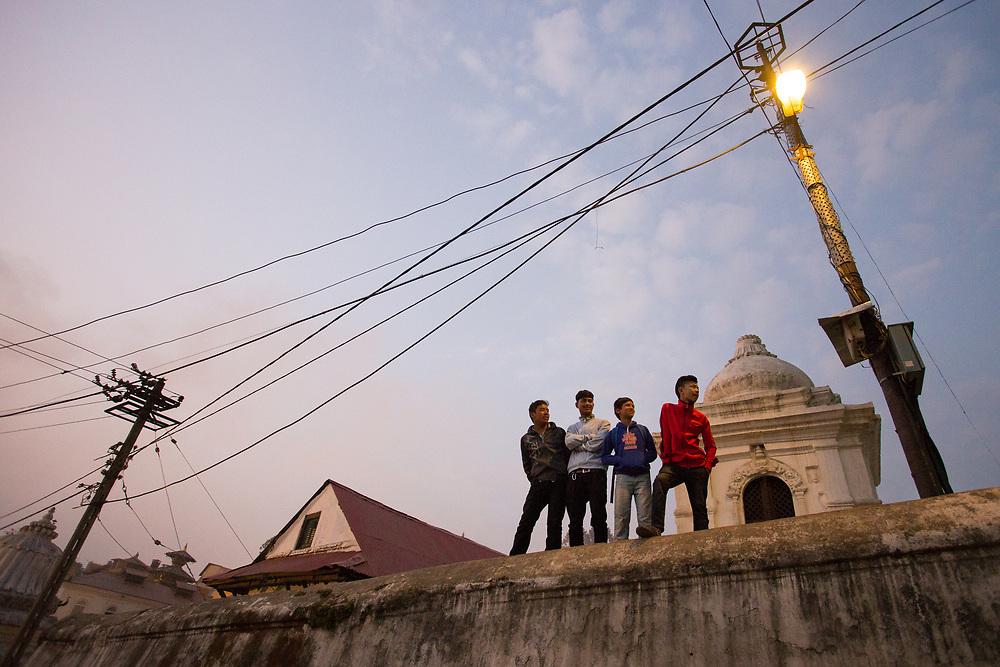Kathmandu, Nepal. A group of friends hanging out on a wall inside the Pashupatinath temple.