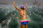 V. 01. Valencia, 25/07/2004. Un partcipante salta al agua con un flotador a la cintura para participar en la travesía a nado del puerto de Valencia. EFE / Kai Försterling.