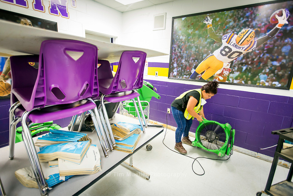 Denham Springs Junior High School clean-up crew member, Suyapa Martinez installs a fan in from school's health room. Clean-up crews are working around the clock to restore the flood damaged school. Livingston Parish School System officials plan to reopen Livingston Parish schools Monday, September 12.