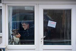 "© Licensed to London News Pictures. 13/01/2017. Jaywick, UK. A man and his dog look out of their window, next to a sign reading ""STAYING PUT!!""  on the seafront at Jaywick where homes were expected to evacuated due to the threat of flooding in low-lying areas . Photo credit: Ben Cawthra/LNP"