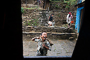 A young boy shouts at his friends through a window in the village of Landruk along the Annapurna Sanctuary Trek, Himalaya Mountains, Nepal.