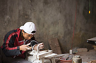 A vietnamese man hand saws a piece of wood in Dong Ky craftvillage, Bac Ninh Province, Vietnam, Southeast Asia