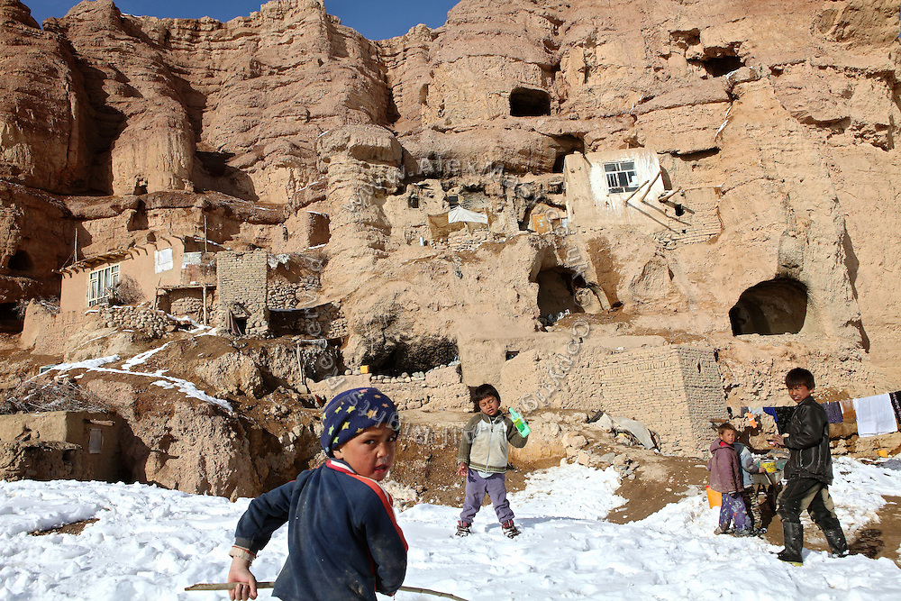 Children are playing in front of an inhabited section of the cliff where once stood the two giant Buddhas of Bamyan, in central Afghanistan, an area mostly populated by Hazaras. A historically persecuted minority (15%) due to more lenient Islamic faith and characteristic 'Eastern' lineaments, Hazaras constitute the 70% of Bamyan's population.