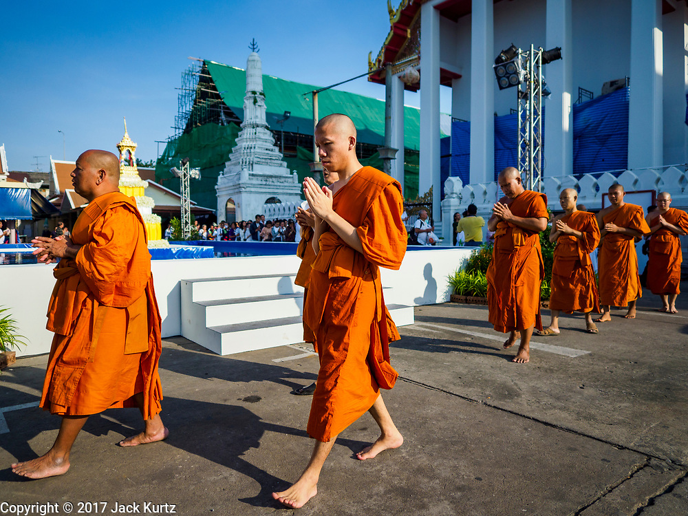 """03 NOVEMBER 2017 - BANGKOK, THAILAND: Buddhist monks participate in a procession at the beginning of Loi Krathong at Wat Prayurawongsawat on the Thonburi side of the Chao Phraya River. Loi Krathong is translated as """"to float (Loi) a basket (Krathong)"""", and comes from the tradition of making krathong or buoyant, decorated baskets, which are then floated on a river to make merit. On the night of the full moon of the 12th lunar month (usually November), Thais launch their krathong on a river, canal or a pond, making a wish as they do so. Loi Krathong is also celebrated in other Theravada Buddhist countries like Myanmar, where it is called the Tazaungdaing Festival, and Cambodia, where it is called Bon Om Tuk.     PHOTO BY JACK KURTZ"""