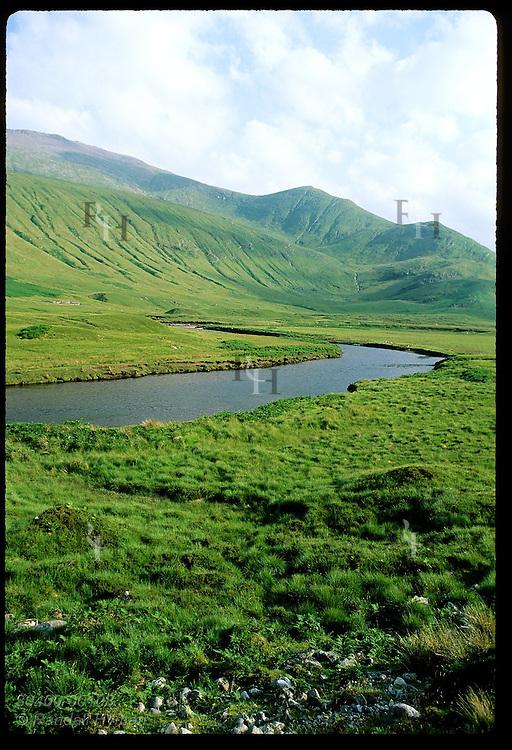 River cuts through lush foothills in mountainous terrain of northwestern Scotland. (v) Scotland