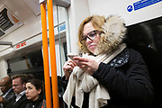 Commuter checking her iPhone on an Overground train during rush hour, South London, UK. This is one of the newer public transport lines on the TFL network.
