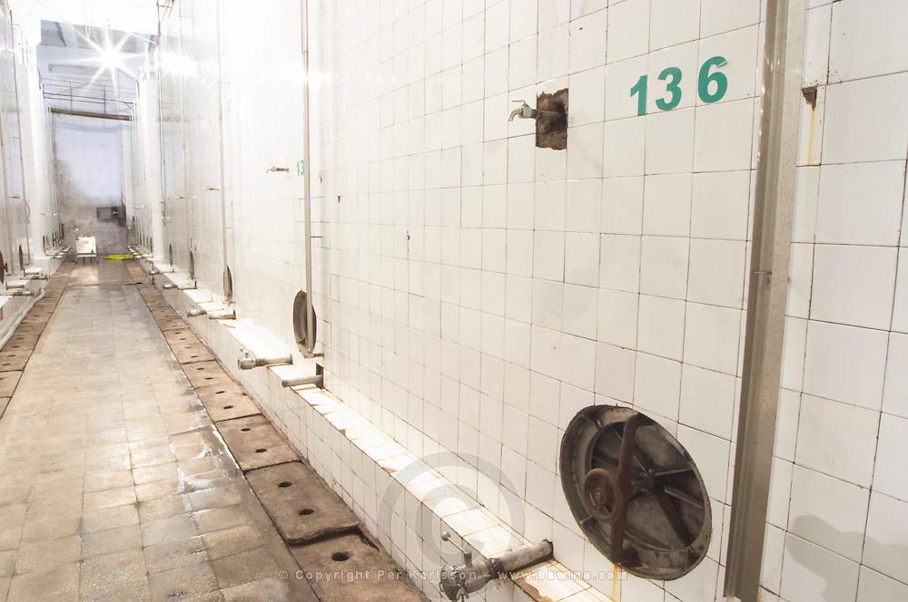 Enormous concrete fermentation and storage vats covered in white tiles. Number 136. Kantina e Pijeve Gjergj Kastrioti Skenderbeu Skanderbeg winery, Durres. Albania, Balkan, Europe.