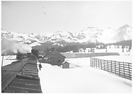 """A winter view of RGS snowshed, section house and stock pens at Lizard Head from atop a freight train caboose.  Photo is captioned """"Phillips hands up orders at Lizard Head"""".<br /> RGS  Lizard Head, CO  Taken by Rasmussen, Forest - ca. 1948<br /> In book """"Rio Grande Southern II, The: An Ultimate Pictorial Study"""" page 273<br /> Also at RD137-075."""
