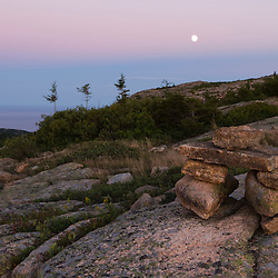 The moon rises as night falls on the North Ridge Trail on Cadillac Mountain in Maine's Acadia National Park.