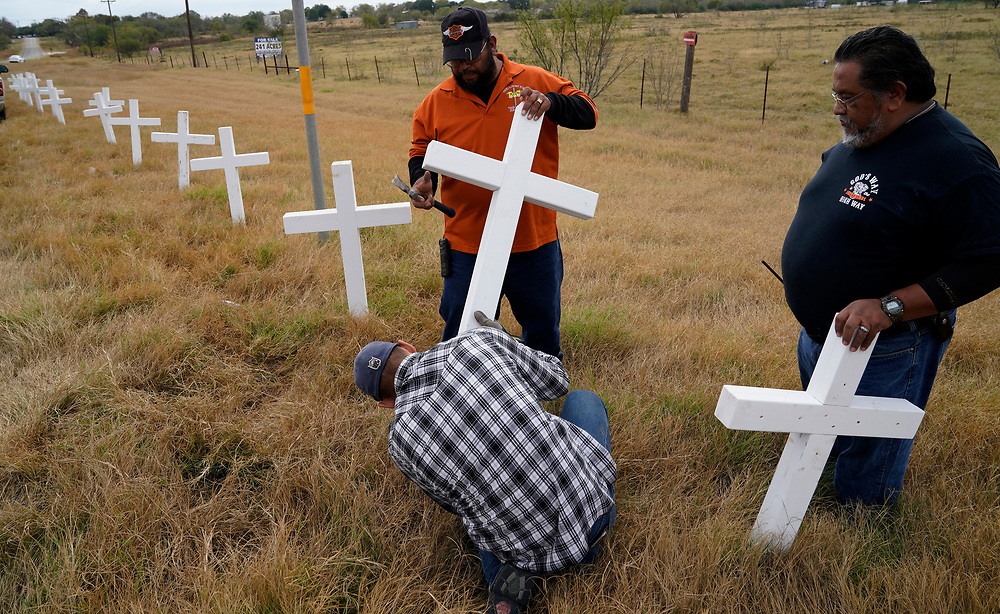 Chris Alcala (L) and Albert Zapata (R) with J.D. (lower) erect a line of crosses along the highway on the outskirts of the town where the shooting took place at the First Baptist Church of Sutherland Springs, Texas, U.S. November 11, 2017.  REUTERS/Rick Wilking