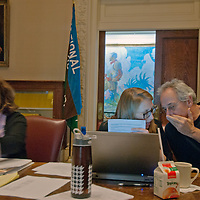 """The National Geographic Expeditions Council Advisory Board member Michael K. """"Nick"""" Nichols whispers about a grant proposal with Program Director O'Shannon Burns during the Council's 2011 meeting in the formal boardroom at Society headquarters in Washington DC.  Director Rebecca Martin sits to the left."""