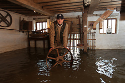© Licensed to London News Pictures. 29/11/2012. Mapledurham, UK. Corry Starling, the miller at Mapledurham Watermill surveys the damage at the last commercially working watermill on The River Thames. A flat belt pulley wheel shows the depth of the water in the ground floor of the mill. The river is about 6 1/2 feet higher than the normal level. Photo credit : Rebecca Mckevitt/LNP