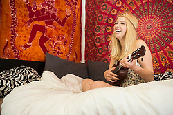 Young woman playing ukulele in the bedroom and laughing, Bavaria, Germany