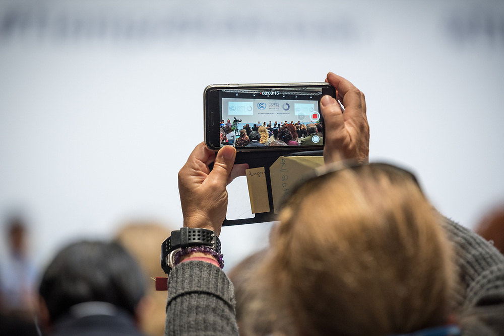 9 December 2019, Madrid, Spain: A man records video during a press conference with Greta Thunberg and Fridays for Future, at COP25 in Madrid.