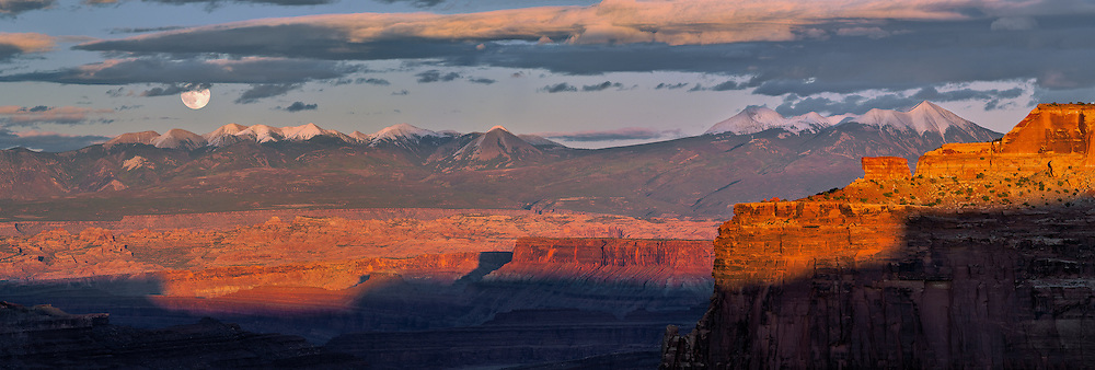 A full moon rises above the LaSal Mountains as the landforms of Canyonlands National Park are bathed in warm sunset light.