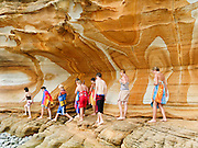 "Young swimmers explore coastal sandstone rock patterns exposed in the Painted Cliffs, in Maria Island National Park, near Darlington, Tasmania, Australia. Undercut by the Tasman Sea (South Pacific Ocean), the Painted Cliffs date from the Permian and Triassic, 300-200 million years ago. Published in ""Light Travel: Photography on the Go"" book by Tom Dempsey 2009, 2010."