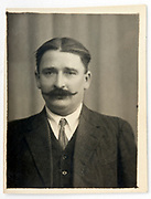 vintage identity style head and shoulder portrait of a adult man with a mustache