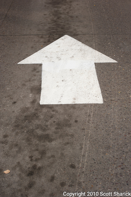 A white arrow is painted on the concrete floor of a parking garage to guide drivers. Missoula Photographer