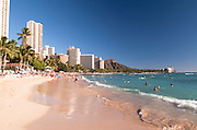 The waves wash up on Waikiki Beach with Diamond Head in the distance.