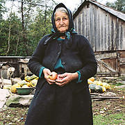 Portrait of a Romanian peasant farmer holding organically grown onions at her smallholding, Sarbi, Maramures, Romania. 90% of vegetable production is grown in small household plots and mainly used for self-consumption and for sale on local markets.