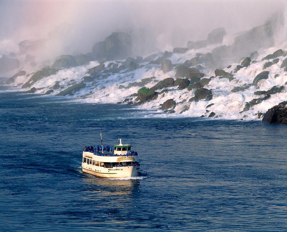 Maid of the Mist skims through the cold waters near Niagara Falls, New York, followed by a rainbow.