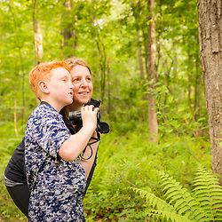 A woman and her son bridwatching in a forest at the Donibristle Reservation in Topsfield, Massachusetts.