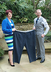 James Quinn, 45, and his wife Joyce 47 hold up the trousers he was wearing in 2011,  before he had lost 15 st 12 and half ,101kls, and while she lost 4st 5pound, 28 kls, after they were named Slimming World Couple of year, UK, Friday March 15, 2013. Photo by Max Nash / i-Images...