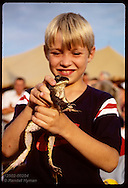 Boy carries his bullfrog to Frog Jump Contest during Tom Sawyer Days, July 4th weekend, Hannibal Missouri