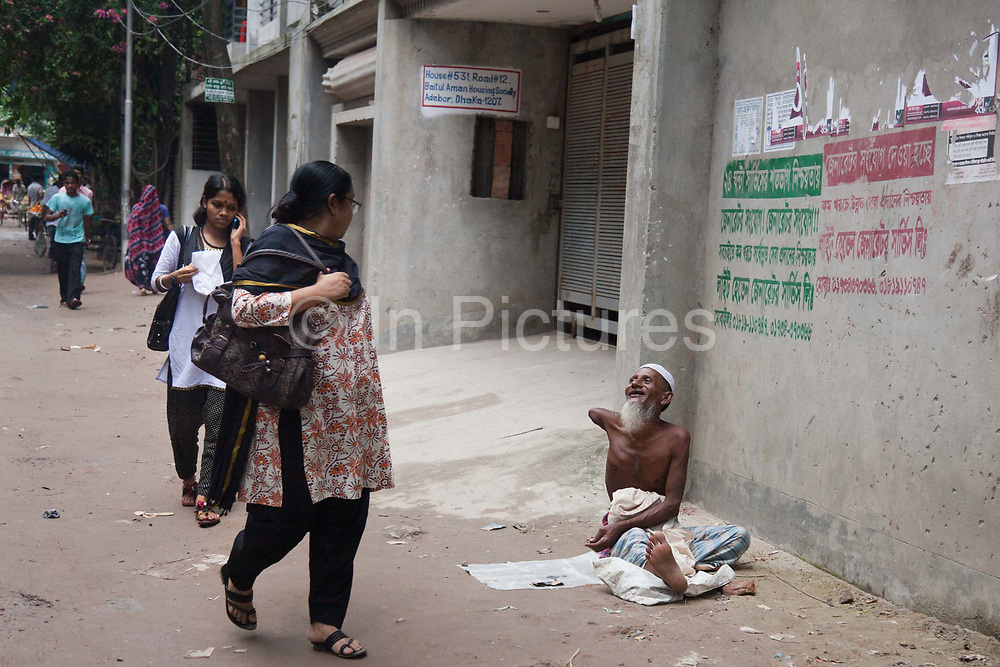 A disabled beggar greets some of his local friend as they pass by. Many disabled people in Dhaka take up begging in stead of work or education as it can be a relative good income. Getting a job or an education being disabled can also be incredibly difficult and begging is to many an easy way to earn a little money.