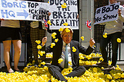 A man dressed as Boris Johnson sits amongst 2000 rubber ducks during a protest by  Pro Remain campaigners Our Future, Our Choice OFOC  on the door step of Boris Johnson's Campaign HQ in London, United Kingdom on 27th June 2019. They accuse Boris Johnson of ducking the British people by avoiding television debates and the Brexit reality in his bid to become Prime Minister.