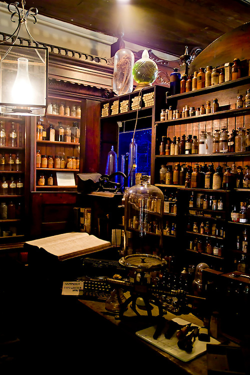 18-19 Century New Orleans Pharmacy Museum's Pharmacy laboratory workroom and worktable. Floor to ceiling shelves of lined up bottles and jars in varying heights surround the room. Hanging lamp with glowing white light inside a large glass jar. Dark blue window in the back corner of the room.
