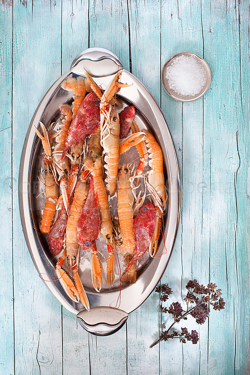 Oval plate with fresh raw lobsters and scorpionfish on wood background, with coarse salt and thyme flowers, top view shot.