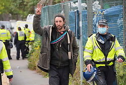 © Licensed to London News Pictures; 20/05/2021; Bristol, UK. A man is led way by police after Bailiffs used a crane to lift him off a scaffold tripod blocking the entrance to the site. Police and bailiffs evict occupants squatting on the site of a former gas works belonging to Wales and West on Glenfrome Road. The site is occupied by around 75 people including children mostly living in vehicles and caravans. Police led some occupants away and released them. The site was evicted last year. Photo credit: Simon Chapman/LNP.