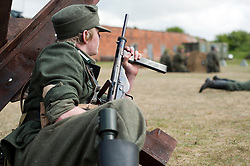 Reenactor portraying a Großdeutschland Panzer Grenadier takes cover behind a tank trap during a battle reenactment at Fort Paull <br />