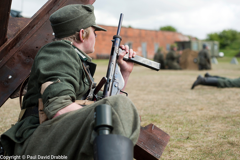 Reenactor portraying a Großdeutschland Panzer Grenadier takes cover behind a tank trap during a battle reenactment at Fort Paull <br /> 2 May 2011<br /> Image © Paul David Drabble