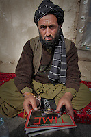 Haji Suleiman, the father in law of Bibi Aisha, with a copy of Time Magazine, in jail in Oruzgan Province, in southern Afghanistan. The magazine cover shows Bibi Aisha, with just a hole and a scar where her nose shout be. Suleiman, 45, is the only man to have been arrested for slicing off Aisha's ears and nose in 2009, as a punishment for running away. Originally from Khush Kadir village, he was arrested in Chora District Centre and brought the provincial capital, Tirin Kot. There are 96 inmates in the prison built for 35, according to the guards. Suleiman, who has not got a defence lawyer, said he is teaching himself to read and write in prison. He has not got a defence lawyer and he insists he is innocent.