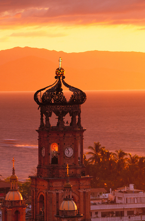 Mexico, Jalisco, Puerto Vallarta. Church tower at sunset (Nuestra Senora de Guadalupe, built 1902) and Bay of Banderas.