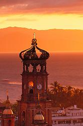Mexico, Jalisco, Puerto Vallarta. Church tower at sunset (Nuestra Senora de Guadalupe, built 1902) and Bay of Banderas.