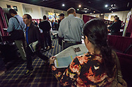 A woman looks over a map listing of bakken region job recruiters at a job fair in Williston, N.D., Oct 3, 2013. Many have traveled to North Dakota seeking oil related jobs, but end up homeless and are forced to survive the frigid winters. Photo Ken Cedeno
