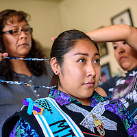 Miss Zuni Tyra Quetawki has her hair wrapped by mother Michele, left, and her aunt Valerie Martinez in Zuni Wednesday.