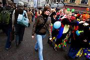 Totaal ongeïnteresseerd loopt een meisje langs een groep carnavalsvierders die bezig zijn met de polonaise