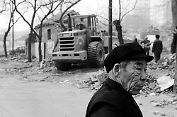 Old Chinese man watching houses in an old hutong being demolished in Beijing China