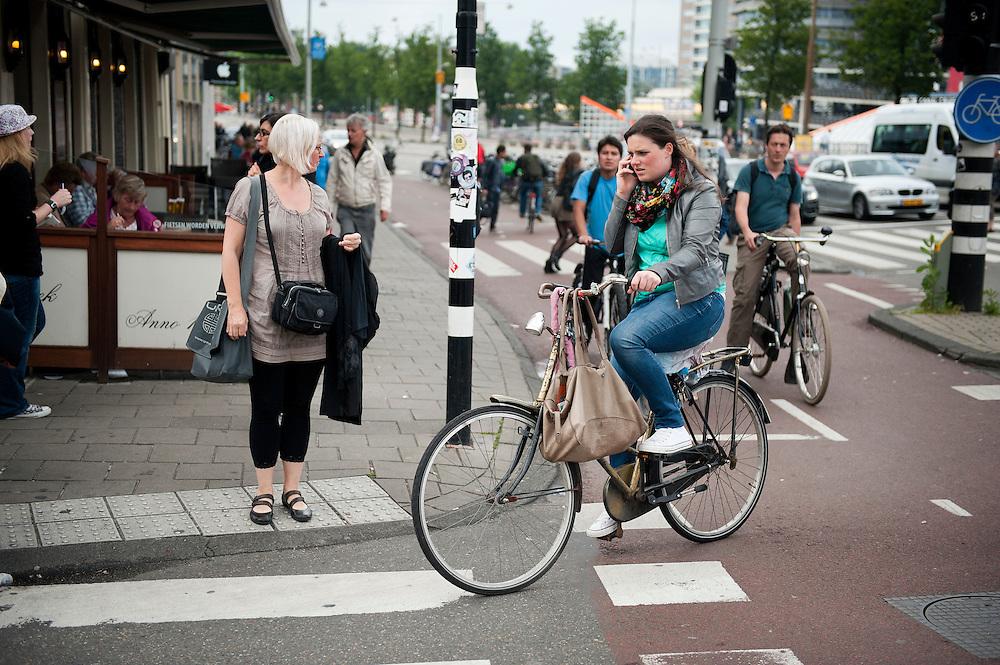 Nederland, Amsterdam, 9 juli 2012.Bellen in het verkeer. Automobilisten moeten handsfree bellen, fietsers bellen gewoon met de telefoon in de hand, midden in het drukke verkeer van amsterdam.Foto (c): Michiel Wijnbergh