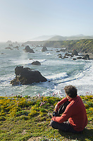 Adult male sitting on bluff edge enjoying view of rugged steastacks rocks and surf of Sonoma Coast State Park, California