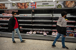 © Licensed to London News Pictures. 21/12/2020. London, UK. Shoppers look at empty shelves of Christmas turkeys and chicken in the meat aisles this afternoon in an Asda in London. Chaotic scenes at Asda in Wandsworth, South West London as a huge rush of shoppers descended on the store causing long queues in the aisles after news that French customs blocked freight from leaving Dover to France after a Covid-19 mutation caused a rapid increase of infection throughout the capital and South East of England. Last week Prime Minister Boris Johnson put London and parts of the South East into Tier 4 lockdown after the new Covid-19 mutation was discovered. Photo credit: Alex Lentati/LNP